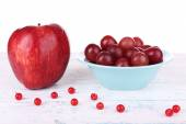 Bowl of red grapes near apple and currants on color wooden surface isolated on white background — Stock Photo