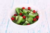 Bowl of slices kiwi with currants on color wooden background — Stock Photo