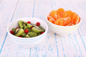 Bowl of slices kiwi and mandarin with currants on color wooden background — Stock Photo