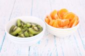 Bowls of slices kiwi and mandarin on color wooden background — Stock Photo