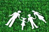 Paper family lying on green grass background — Stock Photo