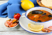 Tasty soup with shrimps, mussels, tomatoes and black olives in bowl on wooden background — Fotografia Stock