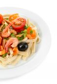 Tasty pasta with shrimps, black olives and tomatoes isolated on white — Stock Photo