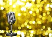 Silver microphone on golden background — Stock Photo