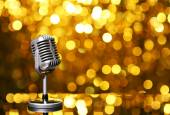 Silver microphone on orange background — Stock Photo