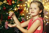 Little girl decorating Christmas tree on bright background — ストック写真