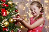 Little girl decorating Christmas tree on bright background — Photo