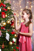 Little girl decorating Christmas tree on bright background — Stock Photo