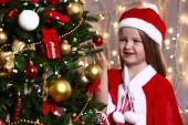 Little girl near Christmas tree on bright background — Stock Photo