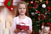 Little girl holding present box near Christmas tree on fireplace with candles background — Stock Photo