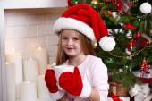 Little girl in Santa hat and mittens taking cup sitting near fir tree on fireplace with candles background — Stock Photo