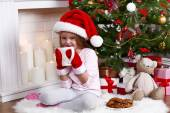 Little girl in Santa hat and mittens taking cup sitting near fir tree on fur carpet and wooden floor, on fireplace with candles background — Stock Photo