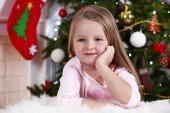 Little girl lying on fur carpet on Christmas tree background — Stock Photo