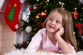 Little girl lying on fur carpet on Christmas tree background — Stock Photo