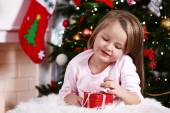Little girl lying with gift on fur carpet on Christmas tree background — Stock Photo