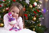 Little girl with mittens lying on fur carpet on Christmas tree background — Φωτογραφία Αρχείου