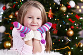 Little girl with mittens lying on fur carpet on Christmas tree background — Stock Photo