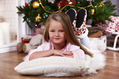 Little girl lying on fur carpet and wooden floor on Christmas tree background — Stock Photo