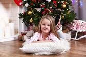 Little girl lying on fur carpet and wooden floor on Christmas tree background — ストック写真