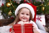Little girl in Santa hat lying on fur carpet on Christmas tree background — Stock Photo