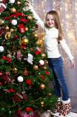 Little girl decorating Christmas tree on bright background — Stock fotografie
