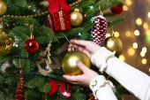 Child's hands hanging bauble on Christmas tree on bright background — Foto de Stock