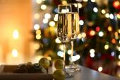 Two glass with champagne with chocolates and baubles on table on Christmas tree and fireplace background — Stock Photo