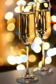 Two glass with champagne on table on bright background — 图库照片