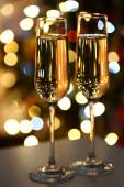 Two glass with champagne on table on bright background — Stock Photo