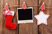 Blank photo frame and Christmas decor on rope, on wooden background — 图库照片