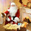 Santa Claus sitting with list of presents in comfortable chair near fireplace at home — Stock Photo #61228323