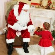 Santa Claus giving  present to  little cute girl near  fireplace and Christmas tree at home — Stock Photo #61228365