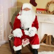 Santa Claus sitting in comfortable chair near fireplace at home — Stock Photo #61228369