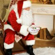 Santa Claus sitting in comfortable chair near fireplace at home — Stock Photo #61228371