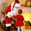 Santa Claus giving  present to  little cute girl near  fireplace and Christmas tree at home — Stock Photo #61228379