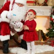 Santa Claus giving  present to  little cute girl near  fireplace and Christmas tree at home — Stock Photo #61228385