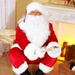 Santa Claus sitting in comfortable chair near fireplace at home — Stock Photo #61228525
