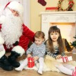 Santa Claus with two little cute girls near  fireplace and Christmas tree at home — Stock Photo #61228613