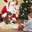 Santa Claus with two little cute girls near  fireplace and Christmas tree at home — Stock Photo #61228617
