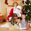 Santa Claus with two little cute girls near  fireplace and Christmas tree at home — Stock Photo #61228619