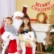 Santa Claus with two little cute girls near  fireplace and Christmas tree at home — Stock Photo #61228677