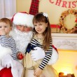 Santa Claus with two little cute girls near  fireplace and Christmas tree at home — Stock Photo #61228685