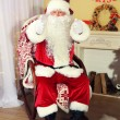 Santa Claus sitting in comfortable chair near fireplace at home — Stock Photo #61228709