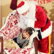 Santa Claus giving  present to sleeping little cute girl Christmas tree at home — Stock Photo #61229001