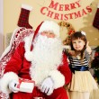 Santa Claus giving  present to  little cute girl near Christmas tree at home — Stock Photo #61229015
