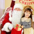 Santa Claus giving  present to  little cute girl near Christmas tree at home — Stock Photo #61229027