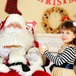 Little cute girl giving glass of milk to Santa Claus near Christmas tree at home — Stock Photo #61229045