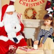 Little cute girl giving glass of milk to Santa Claus near Christmas tree at home — Stock Photo #61229049