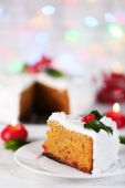 Slice of cake covered cream with Christmas decoration on table, on bright background — Stock Photo