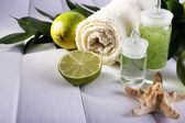 Spa composition with lime and towel color wooden background — Stock Photo
